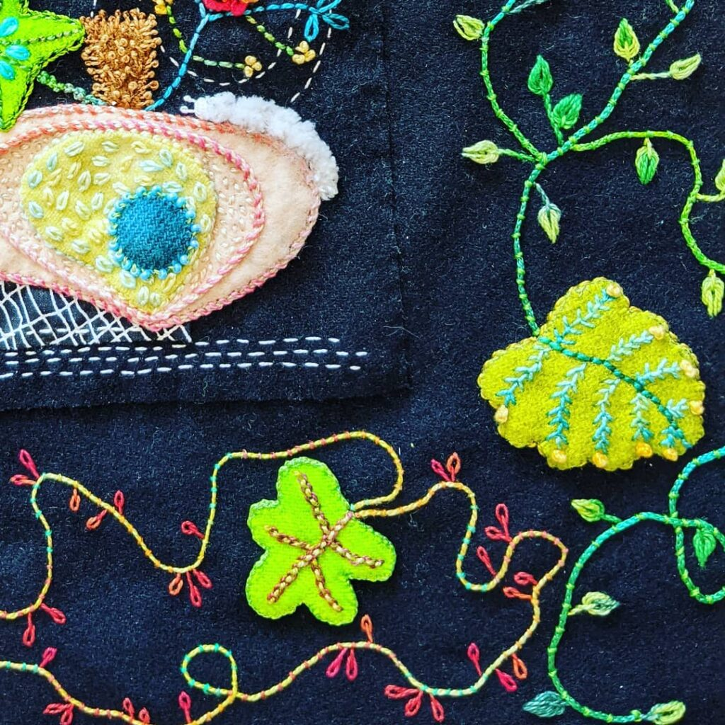Close-up of corner border on my Squash Squad hand embroidered wall hanging from @suespargo. I have the border half done.  #jctextileart #pinegrovenovascotia #handembroidered #squashsquad #woolapplique #valdanithreads #vines #lockdown2020 #lockdownembroidery #suespargo #suespargothreads